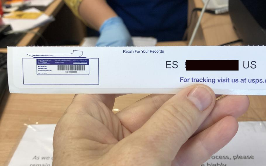 A customer holds up an express mail tracking number for a ballot for the U.S. elections sent from the Army Post Office at Kleber Kaserne in Kaiserslautern, Germany, on Oct. 1, 2020.