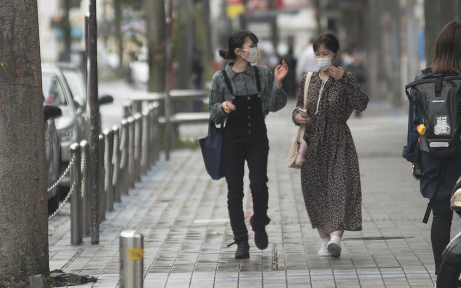 People wear masks to guard against the coronavirus while strolling in Yokosuka, Japan, Sept. 23, 2020.