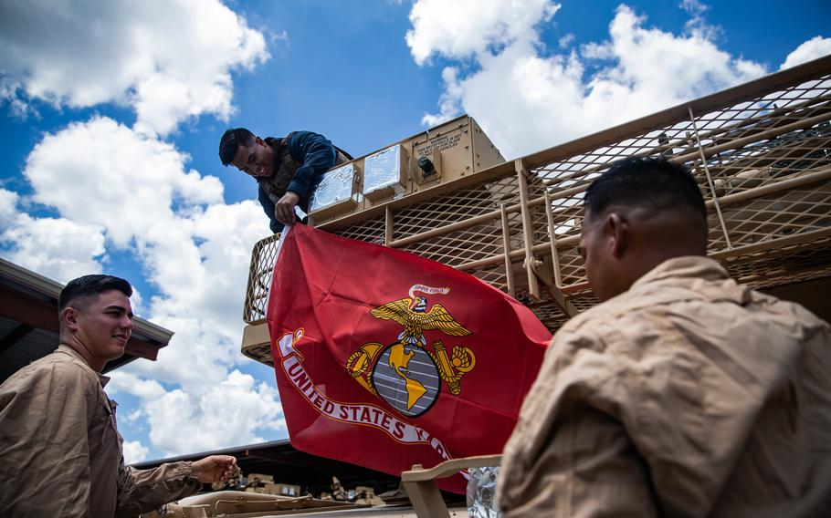 U.S. Marine Corps 1st Lt. Seth Gillen, left, Cpl. Jonathan Villanueva, middle, and Staff Sgt. Stephen Leon Guerrero, with 2nd Tank Battalion, 2nd Marine Division, hang a Marine Corps flag on the rear of an M1A1 Abrams tank on Camp Lejeune, N.C., July 27, 2020.