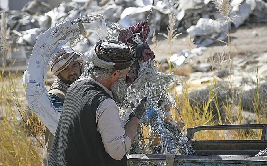 Two workers untangle barbed concertina wire on Saturday, Oct. 31, 2020, in Kandahar, Afghanistan, at a bazaar where goods that once belonged to U.S. and NATO troops and contractors at Kandahar Airfield are sold to locals.