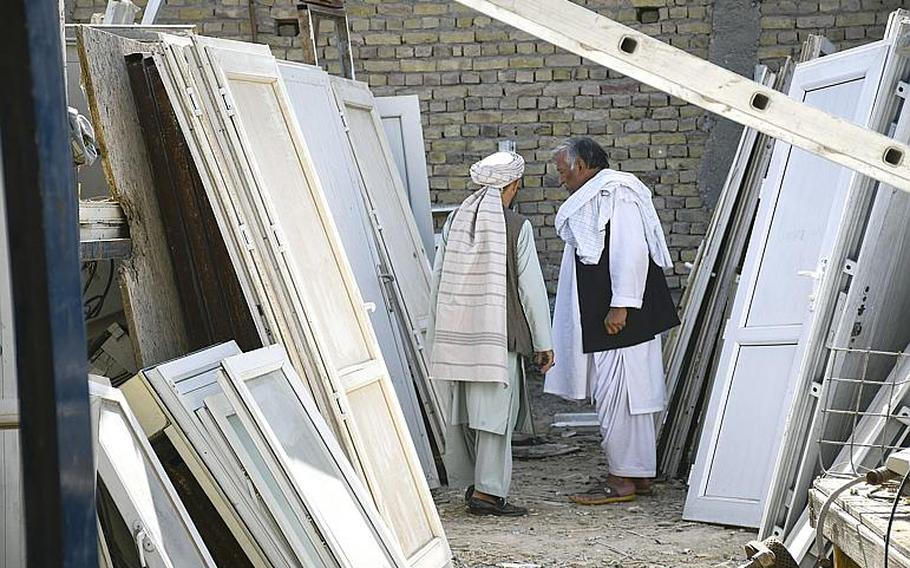Locals in Kandahar, Afghanistan, shop Saturday, Oct. 31, 2020, at ''Bush Bazaar,'' where doors are among the items thrown out by U.S. and NATO troops and contractors that are available for purchase.