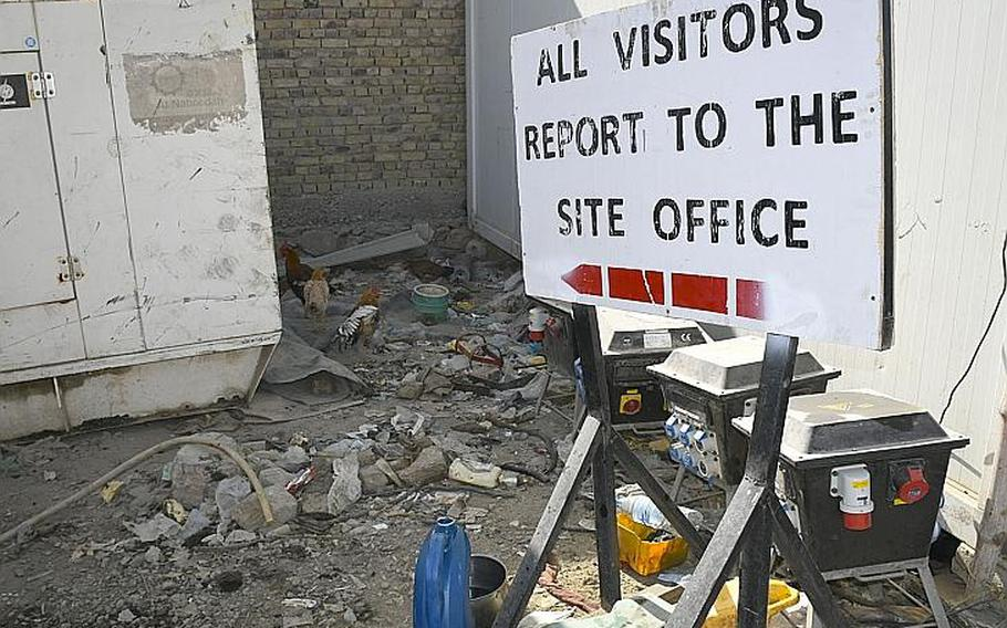 """A sign that once stood at Kandahar Airfield now directs visitors to chickens at a local bazaar where goods from the base are sold to locals. Vendors at the """"Bush Bazaar"""" in Kandahar said containers filled with generators, refrigerators and other valuable goods have been leaving the base as part of the ongoing drawdown of U.S. troops."""