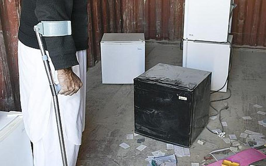 A man shops for refrigerators on Saturday, Oct. 31, 2020, in Kandahar, Afghanistan, at a bazaar where goods that once belonged to U.S. and NATO troops and contractors at Kandahar Airfield are sold to locals.
