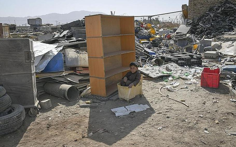 A child sits in a mop bucket hidden in the shade of shelving on Saturday, Oct. 31, 2020, at the ''Bush Bazaar'' in Kandahar, Afghanistan, where items thrown out by U.S. and NATO troops and contractors are available for purchase.