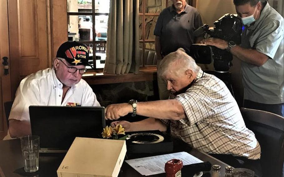 Air Force veteran Richard Pitera, left, and Al Lester look over some photos that Pitera had taken while serving in the Vietnam War.  Lester hosted a luncheon recently to return the photos to Pitera, who is retired and living in Murphy, N.C.