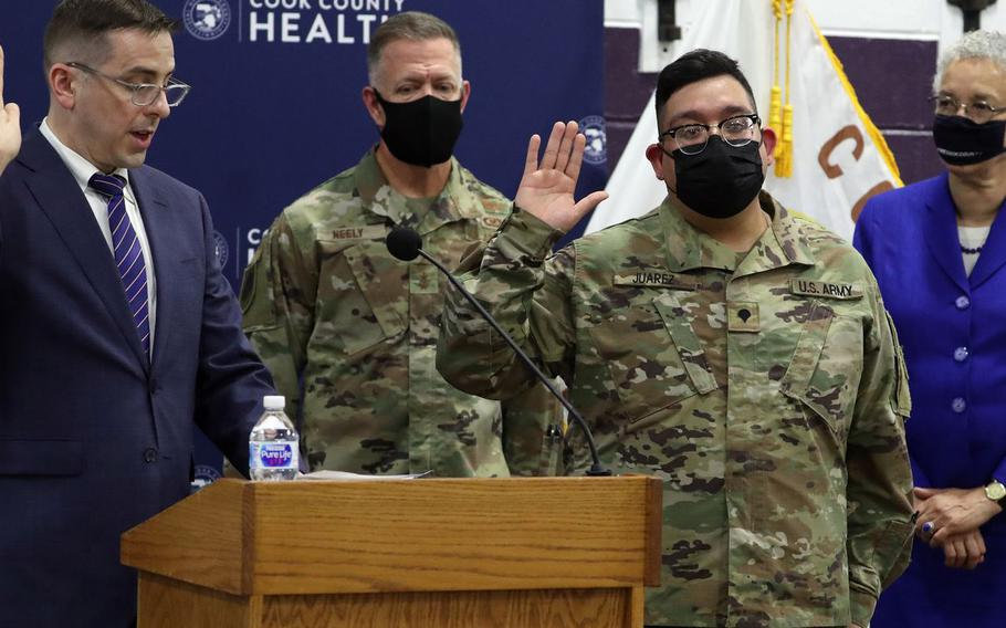 Kevin Riddle, left, Chicago field office director for U.S. Citizenship and Immigration Services, asks Illinois National Guard Spec. Alan Juarez, second from right, to recite the oath of allegiance in a special ceremony at Cook County Health's vaccination site at Thornton Township High School in Harvey on June 10, 2021. Major Gen. Richard Neely, adjutant general of the state of Illinois and Cook County Board President Toni Preckwinkle were on hand..