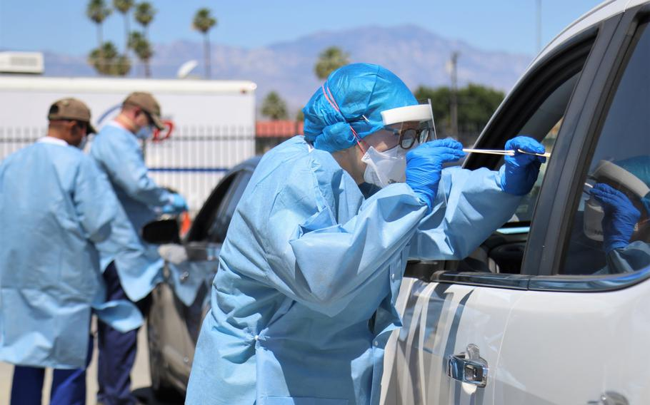 Marcie Richmond, a physician with California Medical Assistance Team, administers a COVID-19 test to a patient at a drive-thru testing site in Indio, Calif., May 19, 2020.