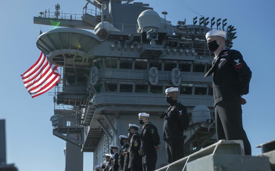 Sailors man the rails on the flight deck of the aircraft carrier USS Nimitz on Feb. 26, 2021.