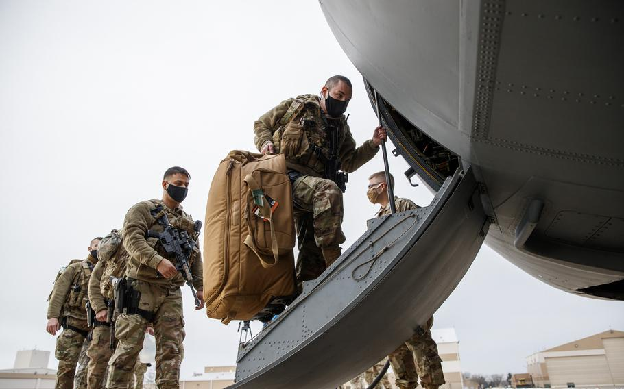 Members of the Illinois Air National Guard's 182nd Airlift Wing security forces board a C-130 Hercules before deploying to Washington D.C., to provide security ahead of President-elect Joseph Biden's inauguration Thursday, Jan. 14, 2021, in Peoria, Ill.