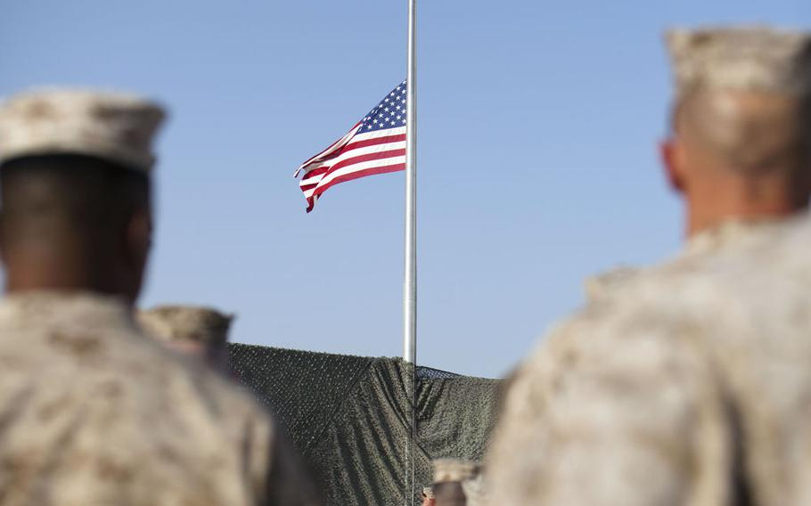 The United States colors fly at half staff at the 9/11 memorial ceremony at Camp Leatherneck, Afghanistan, on Sept. 11, 2011.