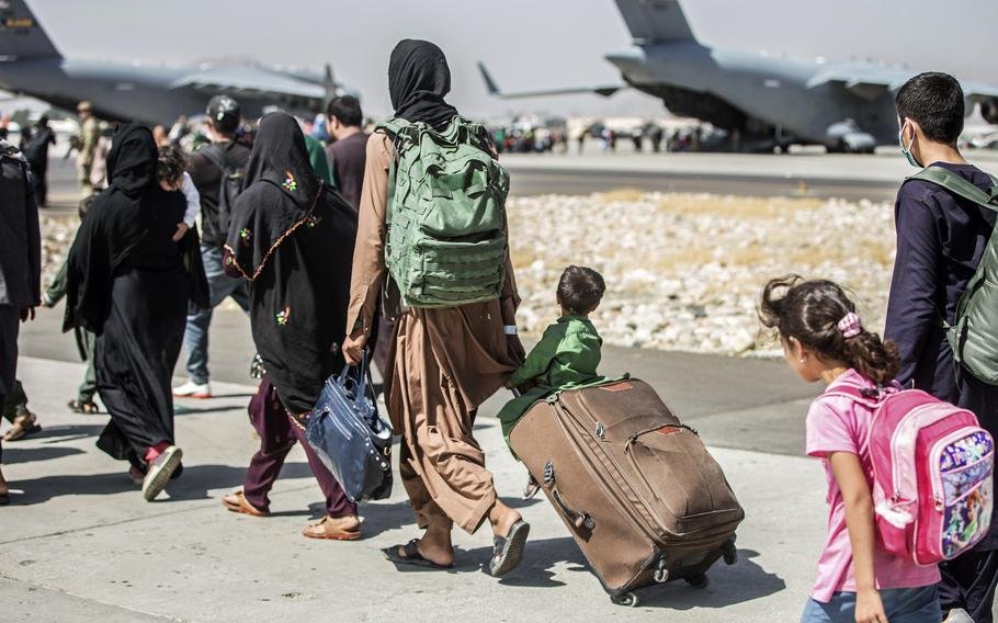 In this Aug. 24, 2021, file photo, provided by the U.S. Marine Corps, families walk towards their flight during ongoing evacuations at Hamid Karzai International Airport, in Kabul, Afghanistan.