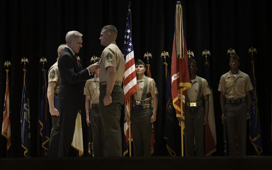 Secretary of the Navy Ray Mabus presents Sgt. Joshua Moore, assigned to 2nd Battalion, 8th Marines, with a Navy Cross medal on Nov. 1, 2013. Moore earned the award for his heroism during combat operations in 2011 while deployed to Marjah, in Afghanistan's Helmand province.