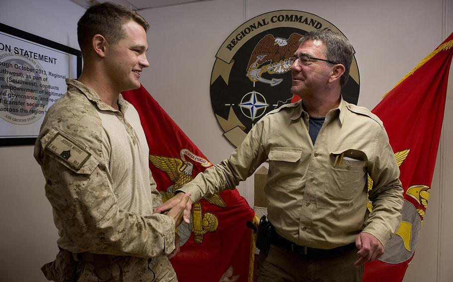 Marine Corps Sgt. Joshua Moore, left, shakes hands with then-Deputy Secretary of Defense Ashton B. Carter at Camp Leatherneck, Afghanistan, on Sept. 13, 2013.