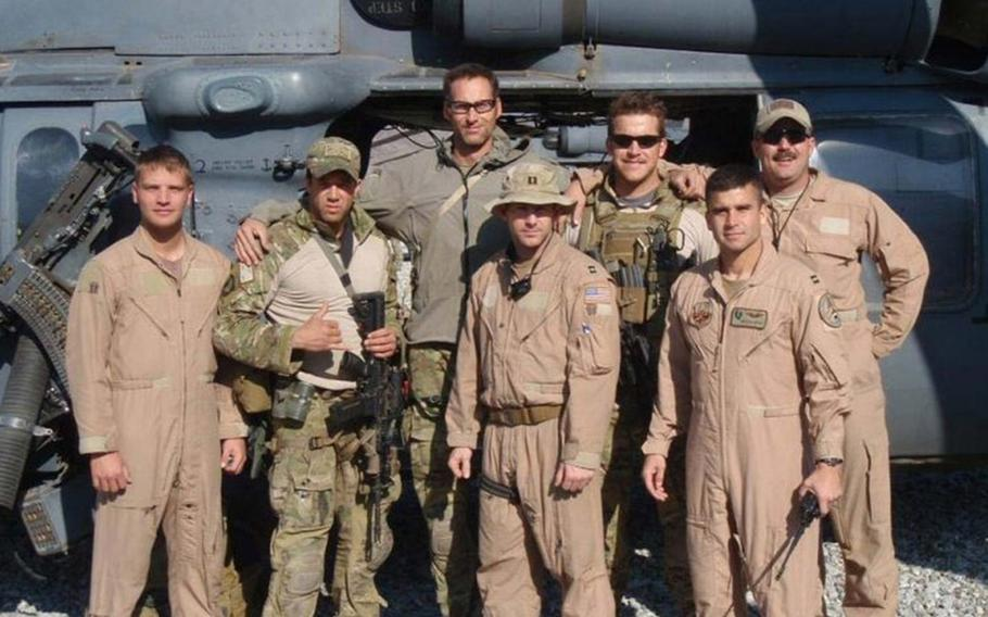 At 6-foot-8, Master Sgt. Roger Sparks towers over the team of pararescue jumpers and pilots he worked with during deployment to Afghanistan in 2010. His right arm is around Capt. Koaalii Bailey, who was on the ground with Sparks on Nov. 14, 2010.