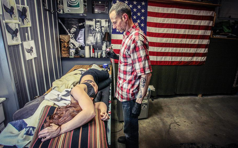 Roger Sparks contemplates the next step of a tattoo.