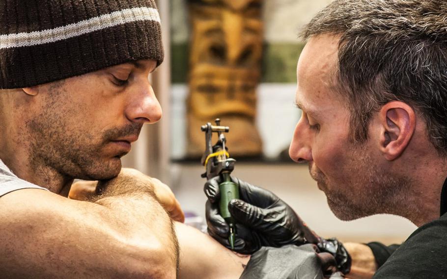 Roger Sparks tattoos a man's arm.