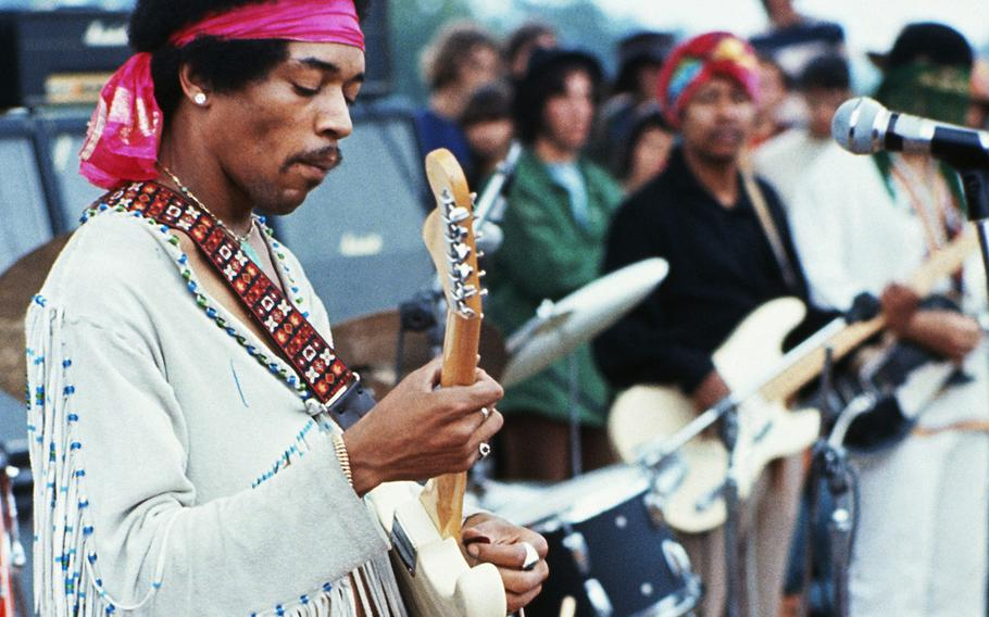 Jimi Hendrix playing his guitar during his set at the Woodstock Music and Art Fair. Playing with Jimi Hendrix is Billy Cox (wearing a turban).