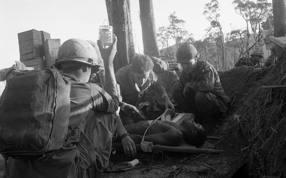 """One soldier holds an IV bottle high up in the air as a medic puts bandages around a chest wound of an unidentified soldier. Men of the 3rd Battalion, 187th Infantry Regiment, 101st Airborne Division had been trying to take """"Hamburger Hill"""" from North Vietnamese forces."""