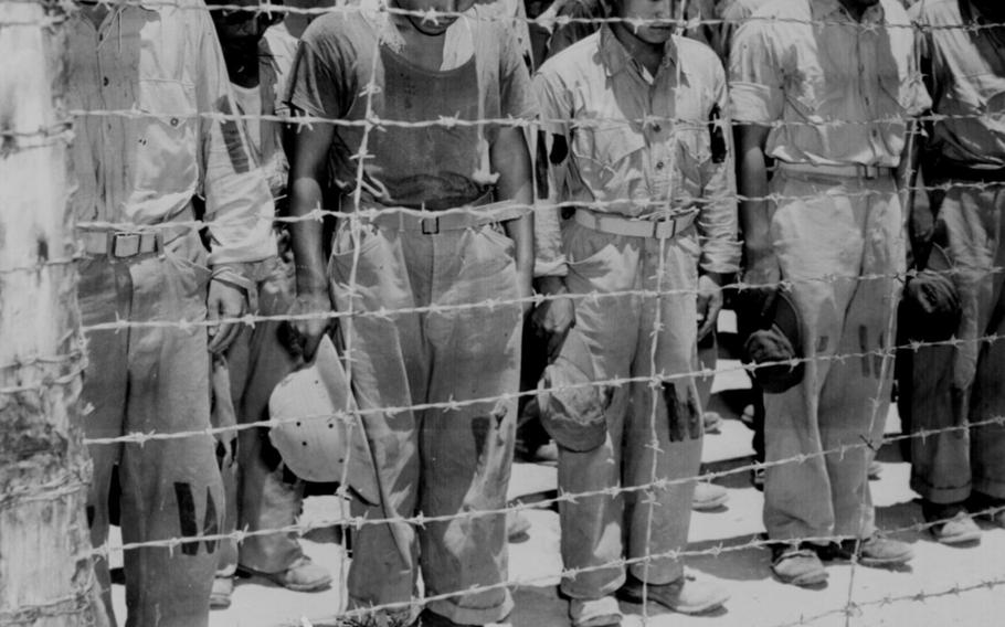 Japanese prisoners of war in Guam bow their heads on Aug. 15, 1945, after hearing that Emperor Hirohito has agreed to Japan's unconditional surrender.