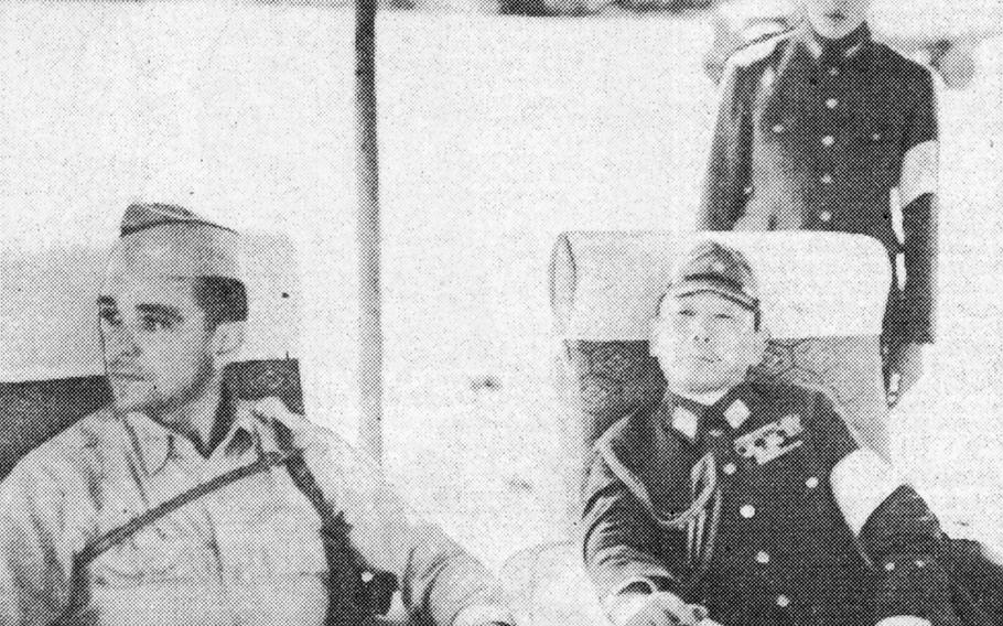 Col. C. H. Tench, left, of General Headquarters for the Supreme Allied Command, confers with Lt. Gen. Seizo Arisuyu after the landing at Atsugi airfield near Tokyo by Americ an Army and Navy representatives.