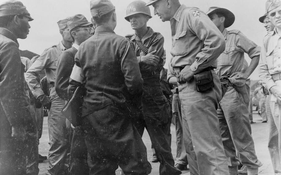 Maj. Gen. Joseph M. Swing, and Lt Gen. Robert L. Eichenberger, speak with Japanese Lt. Gen. Seizo Arisue and 1st Lt. Sadado Otake at the Atsugi Airdrome near Tokyo on Aug. 30, 1945, days before the formal surrender.