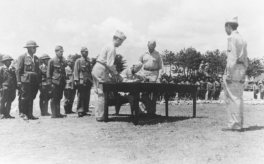 Members of the American delegation signs the terms of surrender of the Ryukyus Island on Sept. 7, 1945 -- five days after the formal surrender of Japan. The Japanese delegation stands in the background.