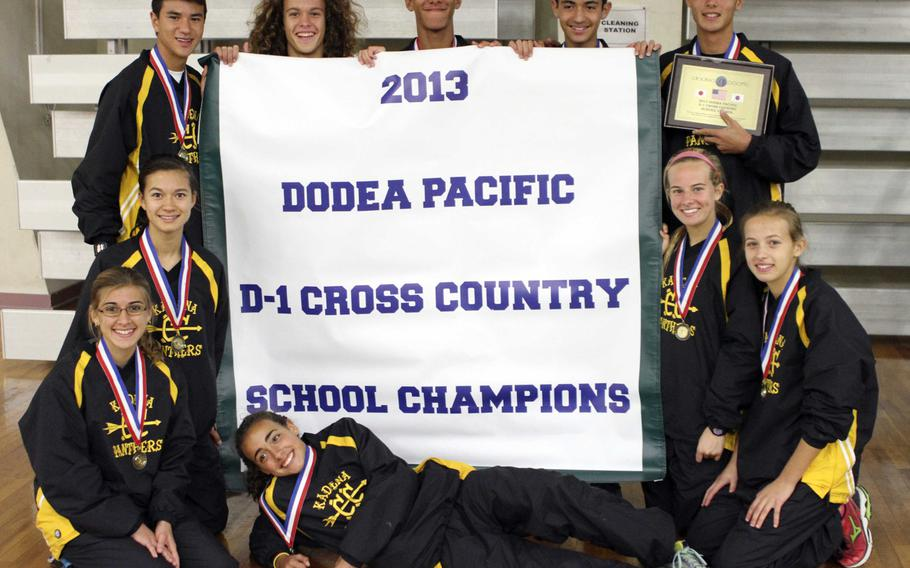 Kadena runners gather 'round the Division I banner inside Halsey Fitness & Sports Center following Tuesday's team relay in the Far East High School Cross-Country Meet at Naval Air Facility Atsugi, Japan. The Panthers won everything there was to be won in the meet, both boys and girls individual races, boys, girls and overall school championships, the team relay points and placed all four of its relay pairs in the top four.