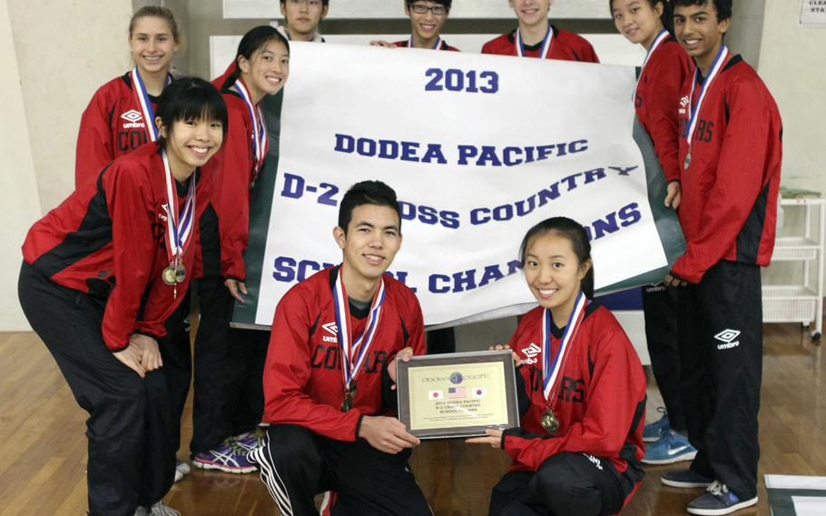 St. Maur International runners gather 'round the Division II banner inside Halsey Fitness & Sports Center following Tuesday's team relay in the Far East High School Cross-Country Meet at Naval Air Facility Atsugi, Japan. The Cougars repeated their overall school championship and won the D-II portion of the team relay, led by two-time Far East champion Lucille Nunnely.