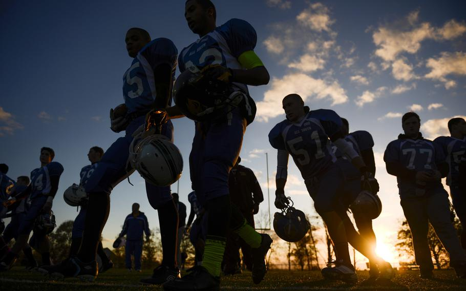 Players from the DODDS-Europe high school football all-star South squad move toward the sidelines before the start of the game Saturday night in Wiesbaden, Germany.