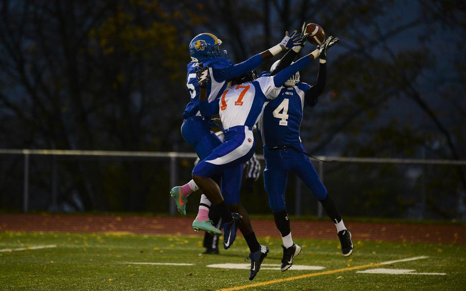 South squad's Jayontray Grogan intercepts a pass intended for North squad's CJ Pridgen with help from teammate Brian Debel ON Saturday night in the DODDS-Europe high school football all-star game in Wiesbaden, Germany.