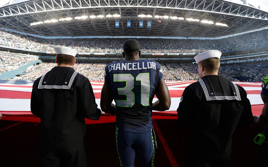Seattle Seahawks' strong safety Kam Chancellor (31) stands with military service members holding a giant U.S. flag before an NFL football game between the Seattle Seahawks and the Minnesota Vikings, Sunday, Nov. 17, 2013, in Seattle.