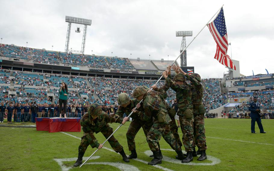 Junior ROTC members perform during a military induction ceremony for new recruits during halftime of an NFL football game between the Jacksonville Jaguars and Arizona Cardinals in Jacksonville, Fla., Sunday, Nov. 17, 2013.