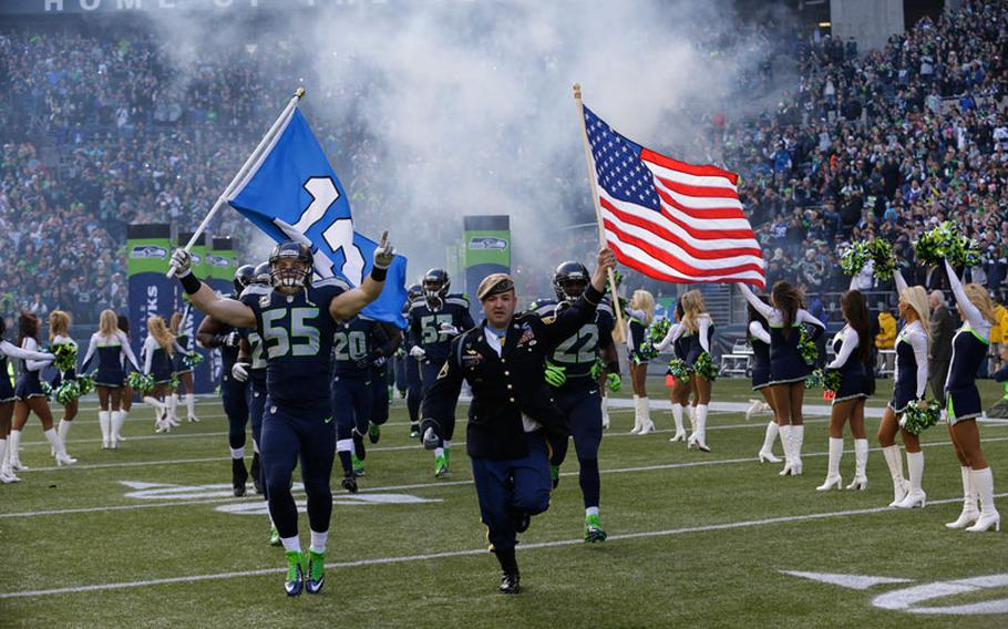 """Seattle Seahawks' linebacker Heath Farwell (55) runs with U.S. Army Sergeant First Class and Medal of Honor recipient Leroy Petry, right, as part of the NFL's """"Salute to Service"""" at the start of an NFL football game between the Seattle Seahawks and the Minnesota Vikings, Sunday, Nov. 17, 2013, in Seattle."""