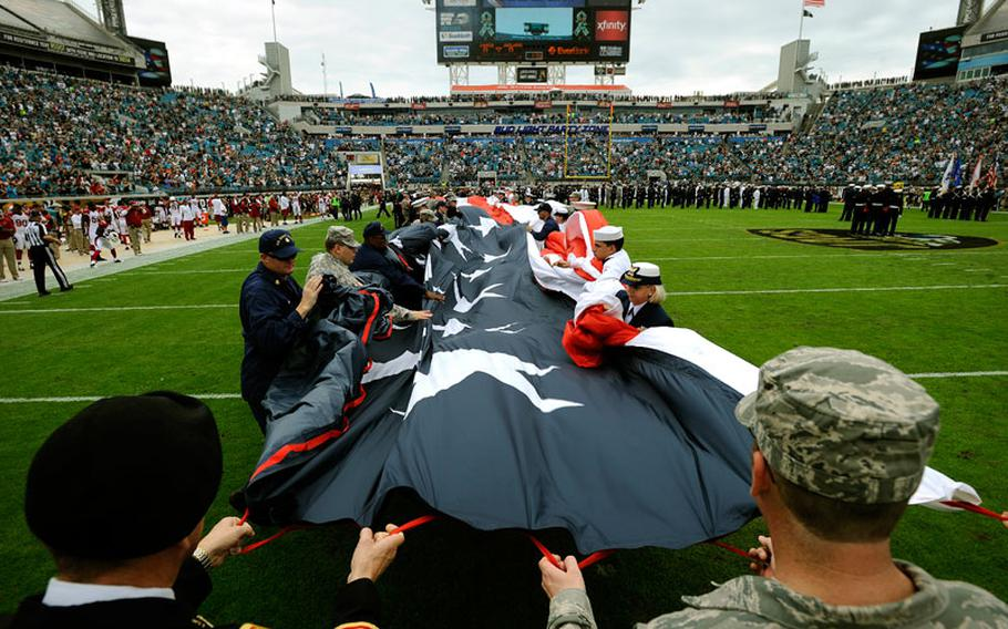 Members of the military gather up a large American flag on EverBank Field before the start of an NFL football game between the Jacksonville Jaguars and Arizona Cardinals, Sunday, Nov. 17, 2013, in Jacksonville, Fla. The Cardinals beat the Jaguars 27-14.