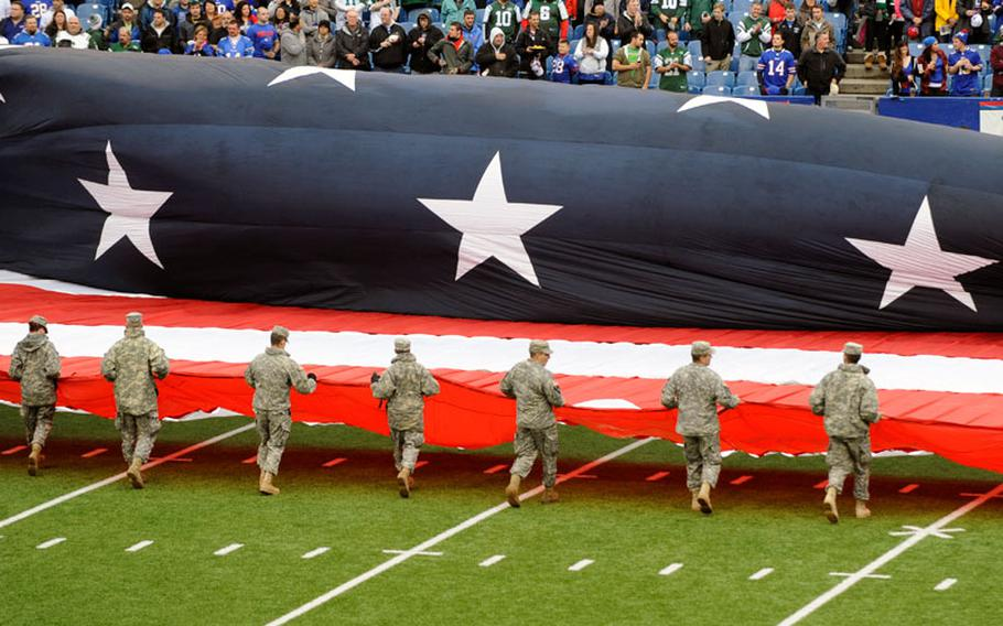 Military personnel unfurl an American flag on the field before an NFL football game between the Buffalo Bills and the New York Jets, as part of the league's Salute to Service initiative, on Sunday, Nov. 17, 2013, in Orchard Park, N.Y.