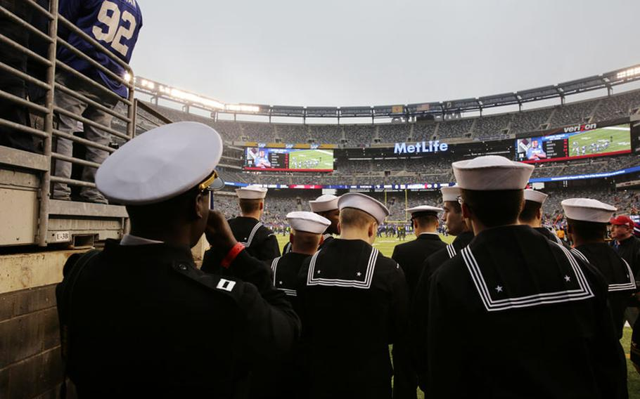Members of the U.S. Navy observe the field at MetLife Stadium before an NFL football game between the New York Giants and the Green Bay Packers Sunday, Nov. 17, 2013, in East Rutherford, N.J.
