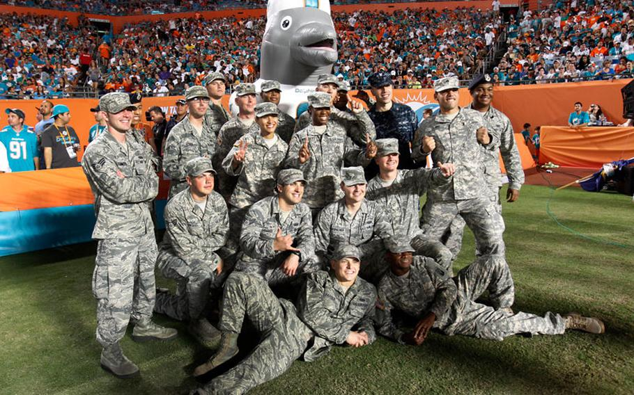 """Service members pose with Miami Dolphins mascot """"Air T.D."""" during a 'Salute to Service' event in the second half of an NFL football game between the Miami Dolphins and the San Diego Chargers, Sunday, Nov. 17, 2013, in Miami Gardens, Fla. The Dolphins defeated the Chargers 20-16."""