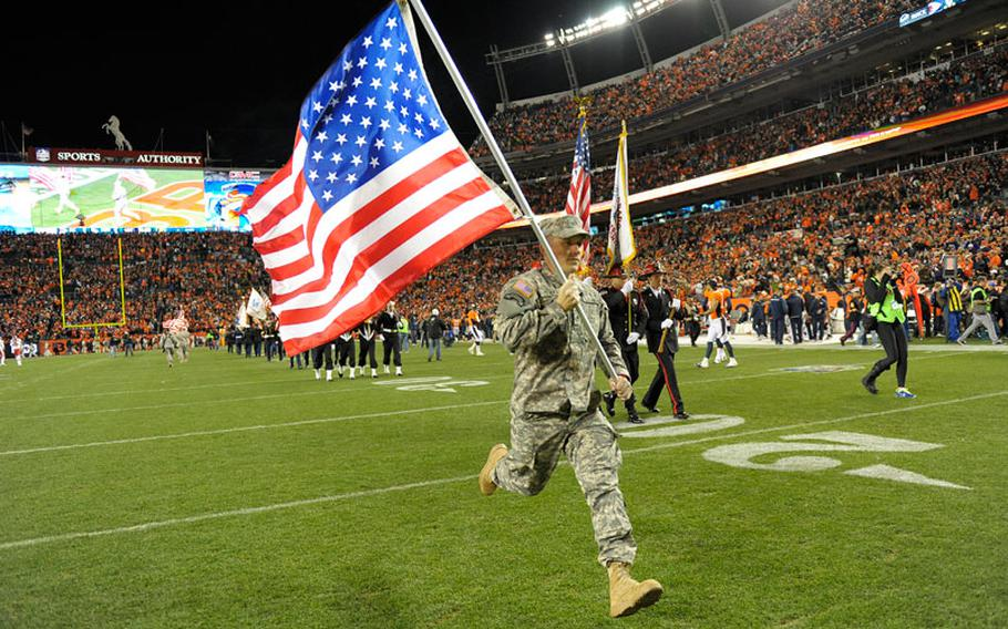 A member of the Army National Guard runs onto the field before an NFL football game between the Denver Broncos and the Kansas City Chiefs, Sunday, Nov. 17, 2013, in Denver.
