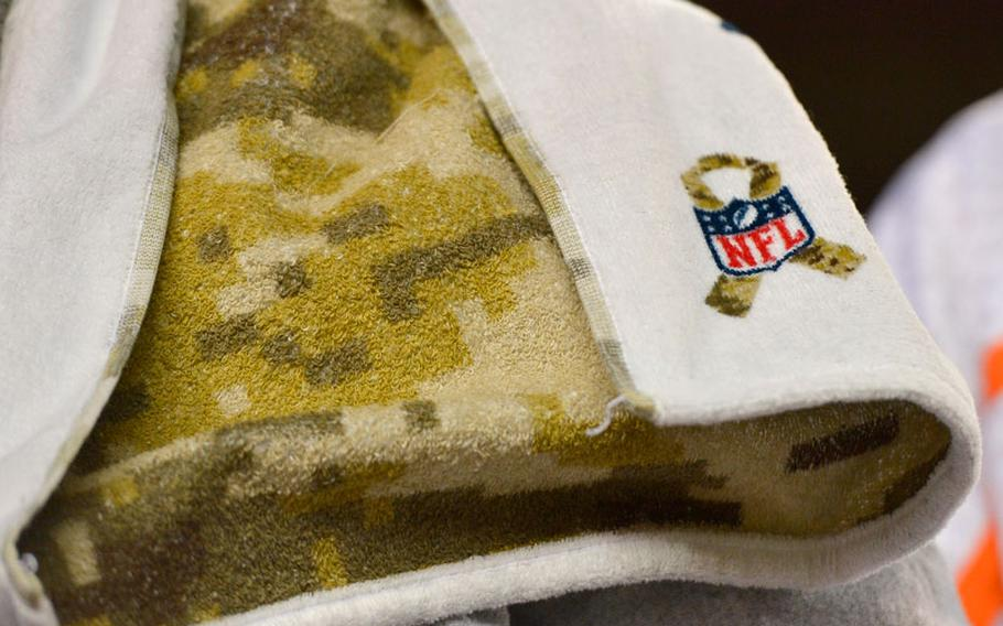 """An NFL logo adorns a camouflage patterned towel on the sidelines before an NFL football game between the Denver Broncos and the Kansas City Chiefs, Sunday, Nov. 17, 2013, in Denver. The Broncos honored members of the military with various """"Salute to Service"""" ceremonies before and during the game."""