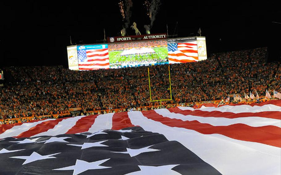A giant American flag is stretched across the field during the national anthem before an NFL football game between the Denver Broncos and the Kansas City Chiefs, Sunday, Nov. 17, 2013, in Denver.