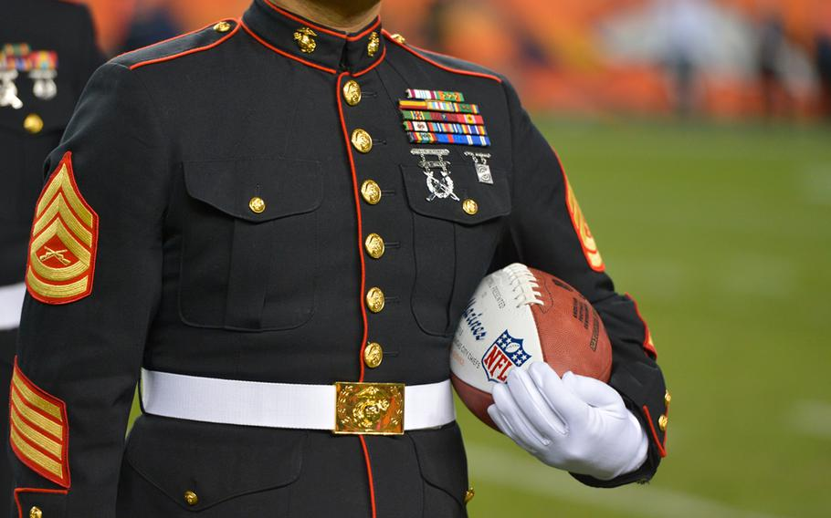 """A United States Marine holds an NFL football during a """"Salute to Service"""" tribute at halftime of an NFL football game between the Kansas City Chiefs and the Denver Broncos, Sunday, Nov. 17, 2013, in Denver."""