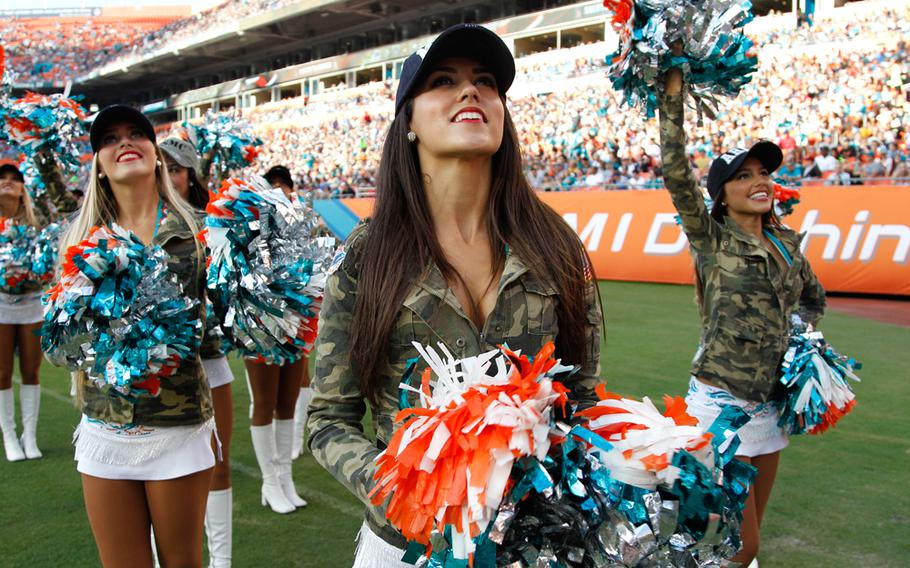 Miami Dolphins cheerleaders perform wearing camouflage jackets in honor of Salute to Service during the first half of an NFL football game against the San Diego Chargers, Sunday, Nov. 17, 2013, in Miami Gardens, Fla. The Dolphins defeated the Chargers 20-16.