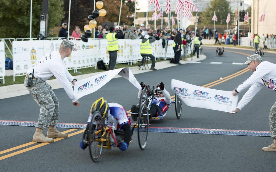 Alber F. Kovach (A11), is the first hand cyclist to cross the finish line at the 30th Army Ten-Miler, October 12, 2014.