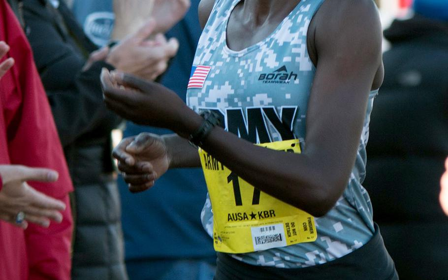 Army Spc. Caroline Jepleting crosses the finish line at the Pentagon Sunday morning as the top military finisher at the 2014 Army Ten-Miler. Jepleting also took second place in the women's division.