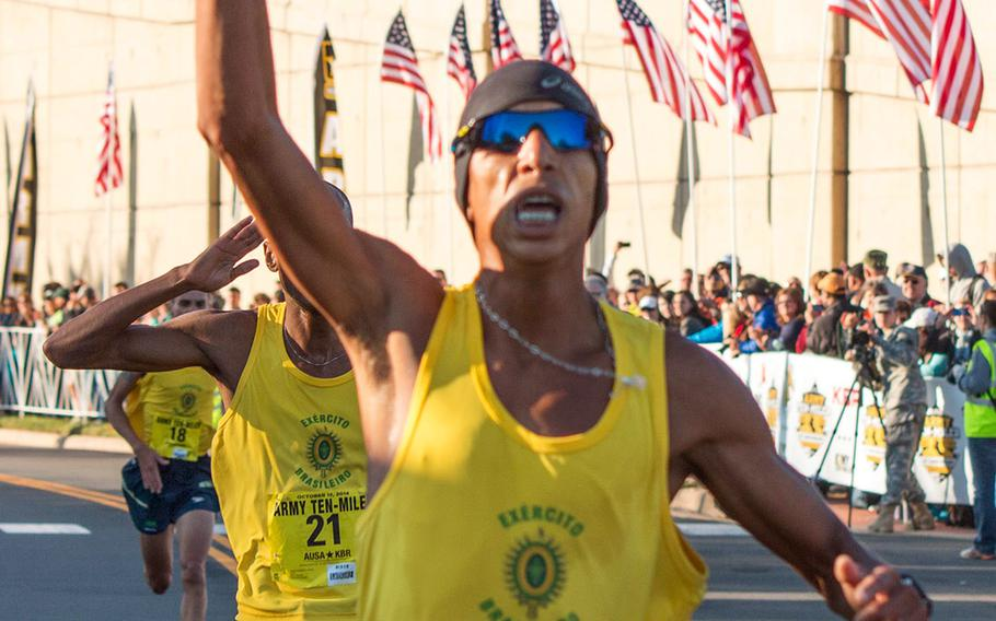 Solonei Da Silva (1) of the Brazilian army crosses the finish line at the Pentagon Sunday morning as the winner of the 2014 Army 10 Miler. Following him across the line are teammates Paulo Roberto Paula (21) and Franck Almeida (18).