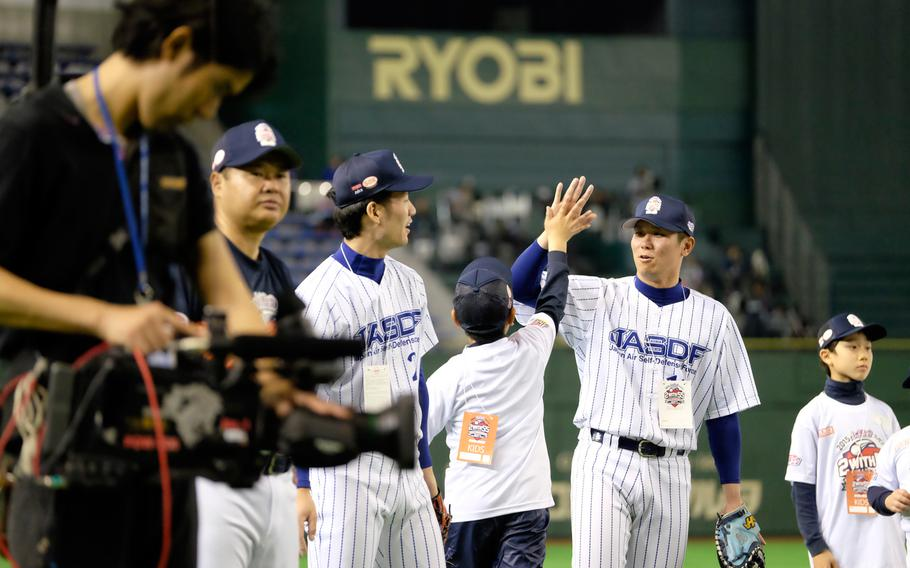 A player from the Japan Air Self-Defense Force team high-fives a young baseball clinic attendee Saturday night, March 21, 2015, at the Tokyo Dome. The clinic was led by former New York Yankees Derek Jeter and Hideki Matsui with volunteers from United States Forces Japan translating.