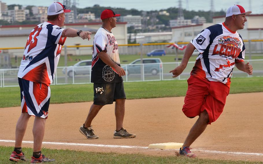 """American Legion's Robert Gullett rounds third base for home past Legion coach John O'Brien and Pour House third baseman Anthony Velarde during Saturday's Game 1 of a two-game men's final in the Firecracker Shootout Softball Tournament. Legion scored five seventh-inning runs and won 9-4, forcing a second """"if necessary"""" game, which Pour House won 13-12 for its second Firecracker title in three years."""