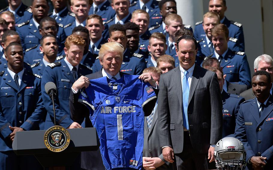 President Donald Trump holds up an Air Force Academy football team jersey in the Rose Garden of the White House on Tuesday, May 2, 2017, during a presentation ceremony of the Commander-in-Chief trophy to the Air Force Academy football team. At right is U.S. Air Force Academy football team coach Troy Calhoun.