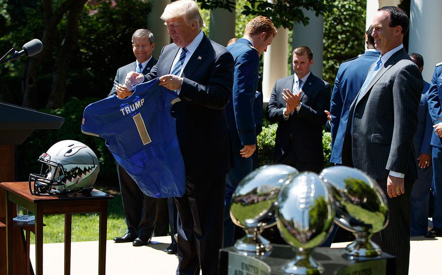 President Donald Trump looks at an Air Force Academy jersey presented to him during a ceremony in the Rose Garden of the White House in Washington, Tuesday, May 2, 2017. The Air Force Academy football team was there for the presentation ceremony of the Commander-in-Chief trophy.