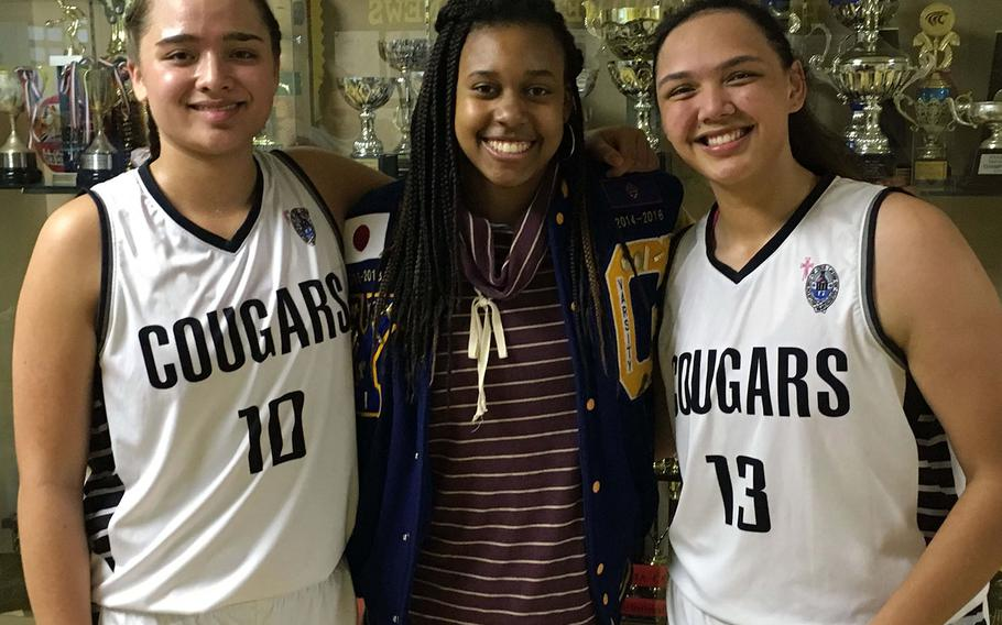"""Rivals reuinted at the 2nd Kanto Classic Basketball Tournament. Academy of Our Lady of Guam's unanimous All-Island MVP Mia San Nicolas and teammate Meaghan """"Mink"""" Cruz flank Yokota senior center Britney Bailey in front of the trophy case at American School In Japan. Bailey played against San Nicolas and Cruz frequently while with Guam High School in her freshman and sophomore seasons. Bailey transferred to Yokota in October 2016. Academy plays Yokota at 4:40 p.m. Friday in the final pool play game."""